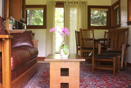 The Tower living room opens onto a deck in the woodland.